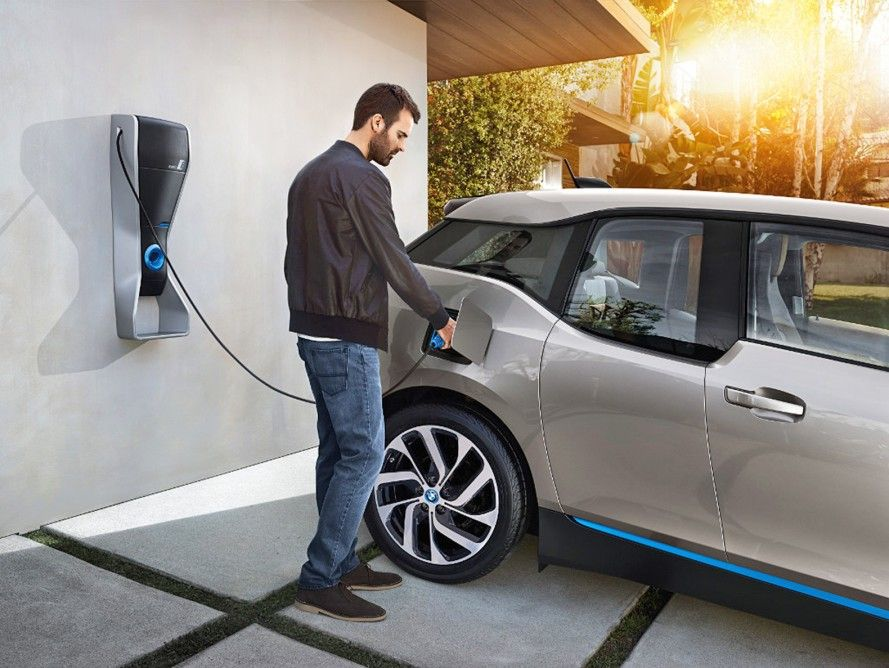 home car charging picture. A man is charging his electric car. Car is silver cover.
